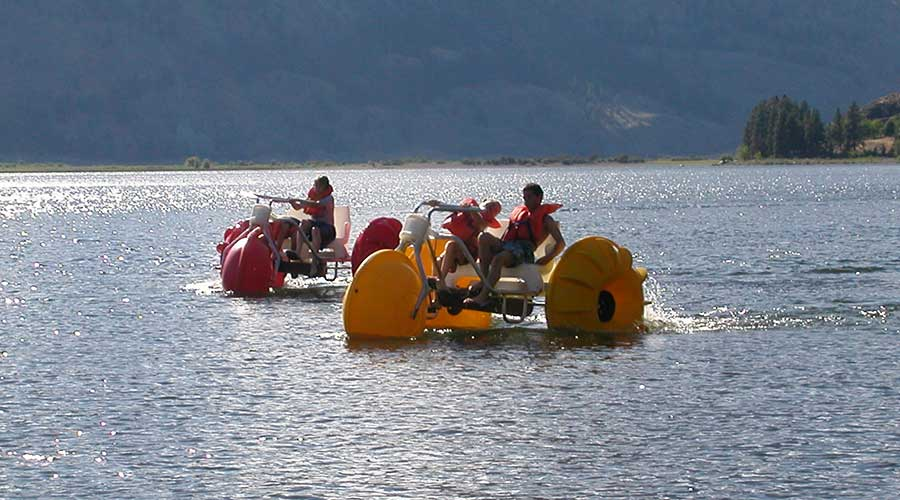 Environmentally friendly yellow and red Aqua-Cycle™ Water Trikes at a lake resort or youth camp rented for good profits by a recreational water equipment rental business.
