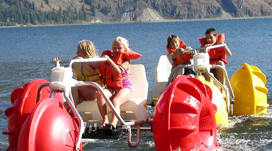 Yellow and red Aqua-Cycle™ Water Trikes at a lake resort or youth camp