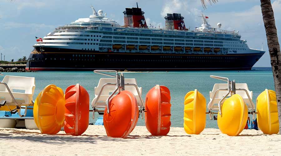 Three beach rental toys called Aqua-Cycles ready for use at a resort with Disney cruise ship in the background.