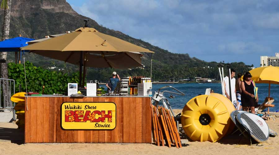 A yellow Aqua-Cycle™ Water Trikes on the beach in Hawaii at a beach services recreational equipment rental company.
