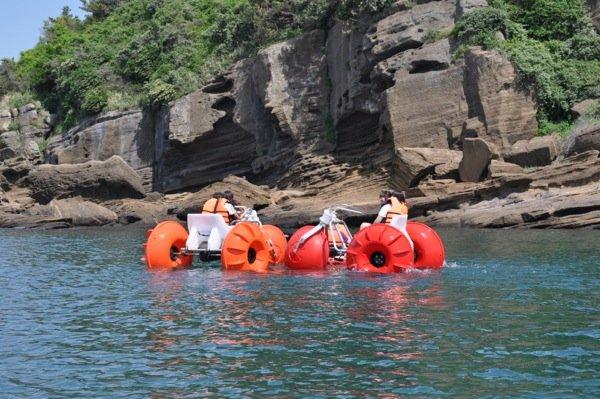 Orange and red Aqua-Cycle™ Water Trikes at a lake resort or youth camp