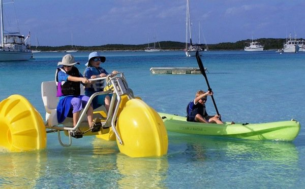 Boys on a water tricycle in a harbor.