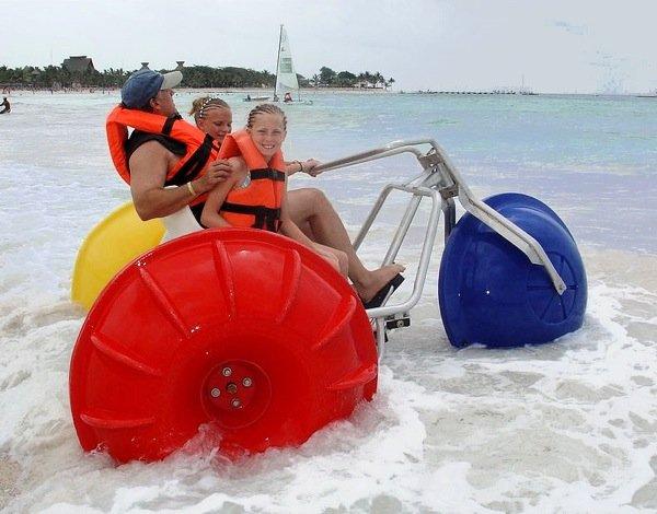 Daughters and dad on an Aqua Trike at a beach resort in the ocean break