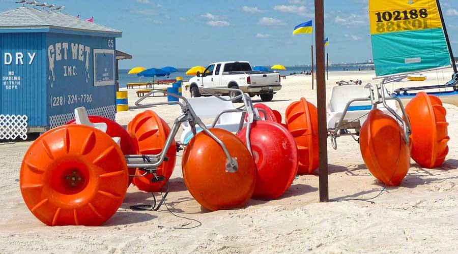 Orange Aqua-Cycle™ Water Trikes at a water beach equipment rental business
