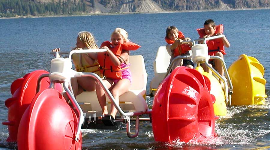 Yellow and red Aqua-Cycle™ Water Trikes at a lake retreat center or youth camp