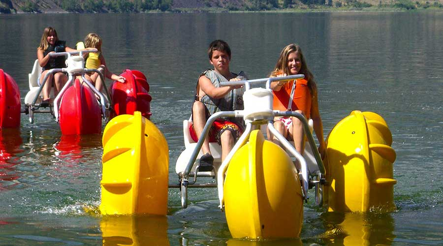Yellow and red Aqua-Cycle™ Water Trikes at a lake retreat center or youth camp Yellow and red Aqua-Cycle™ Water Trikes at a lake retreat center or youth camp