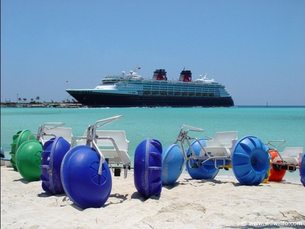 Four beach big wheel water tricycles ready for use with cruise ship in the background