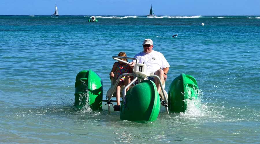 Persons having fun at a beach using Aqua-Cycle water trikes