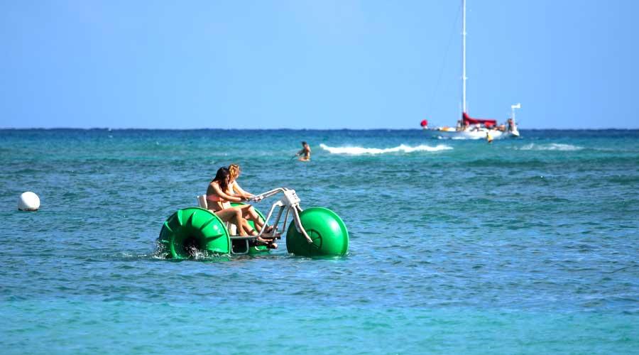 Ladies having fun at a beach using Aqua-Cycle water trikes