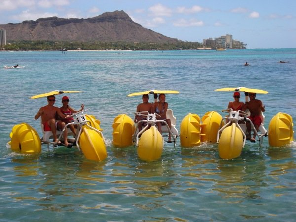 Three yellow Aqua-Cycle™ Water Trikes in Hawaii rented by Waikiki Shore Beach Services in Waikiki with Diamond Head in the background.