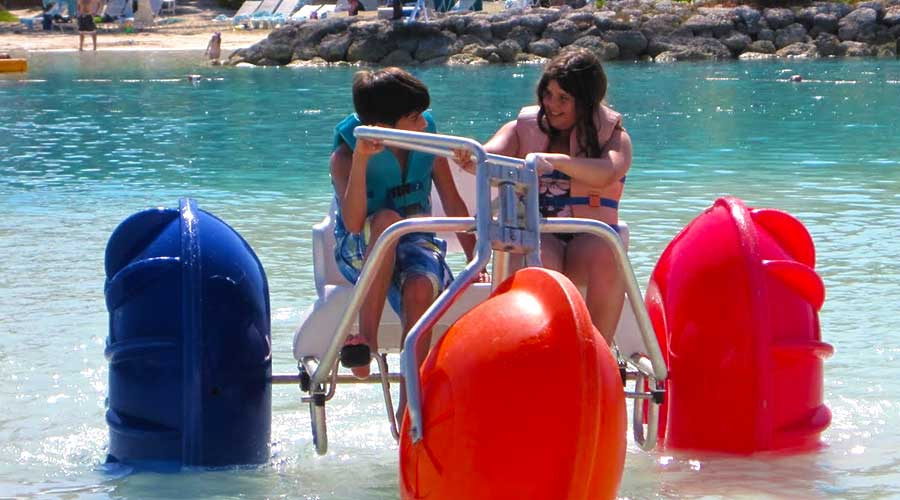 Two kids having fun on a water tricycle at a hotel resort