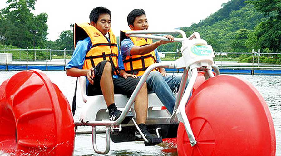 Young men on a three wheeled pedal boat at an island resort
