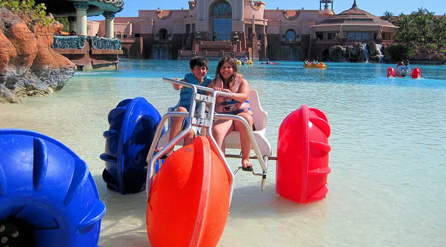 Kids on a blue, orange, and red aqua cycle at an Island Hotel Resort