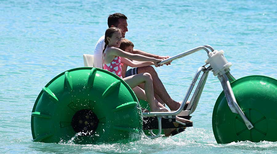 Dad and kids having fun on a water tricycle at an island resort