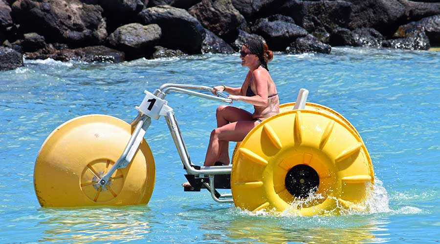 Lady with tattoos having fun on a yellow water tricycle at an island resort