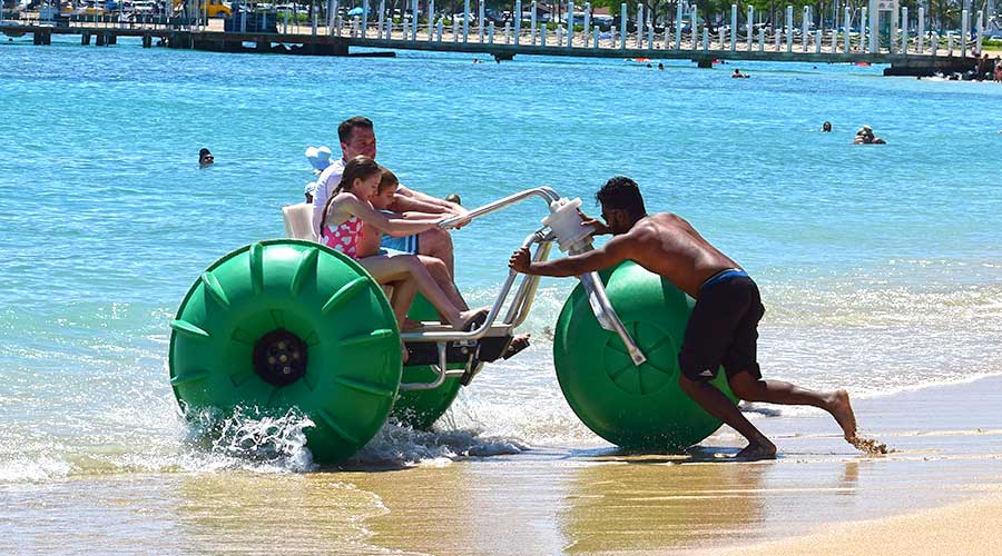 Dad and kids having fun on a water tricycle at an island resort as they get pushed out to sea.
