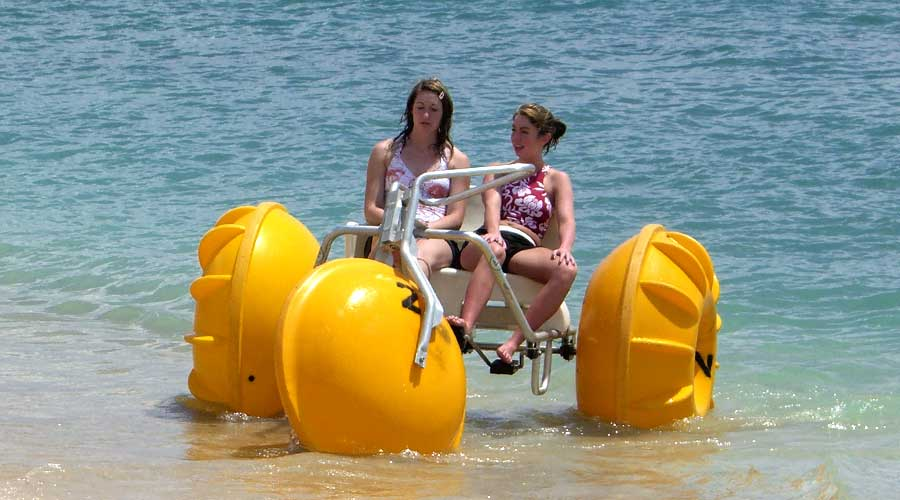 Two teens having fun on a water tricycle at an island resort