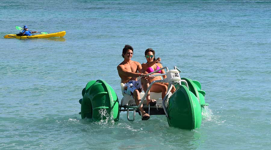 Green Aqua-Cycle™ Water Trikes rented at an island resort by a recreational water equipment rental business.