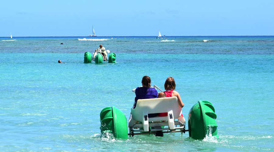 Green Aqua-Cycles rented at an island resort beach rental business in the surf in Hawaii