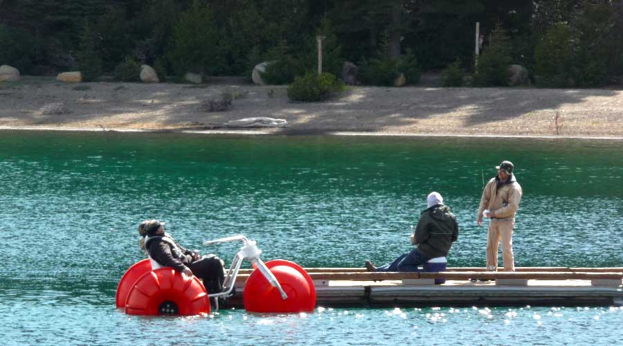 The Aqua-Cycle™ Water Trike with riders talking to fisherman on a dock.