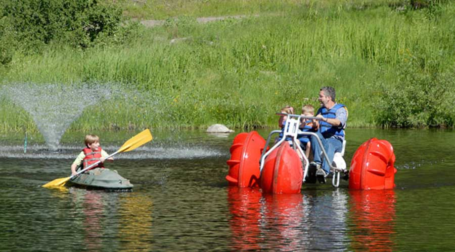 Man and kids on a big wheeled red Aqua-Cycle™ Water Trike at a pond with a boy holding yellow oars alongside the water tricycle.