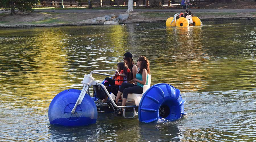 two women and young girl on a big wheeled red Aqua-Cycle™ Water Trikes at a pond at a park recreational facility with another aqua-cycle in the background that is yellow.