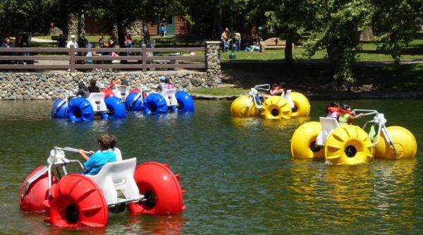 Many big wheeled Aqua-Cycle™ Water Trikes at a pond at a city park.