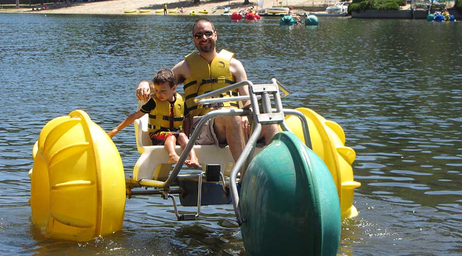 Yellow and green Aqua-Cycle™ Water Trikes rented at a parks and recreational facility in a city with man and boy on tricycle.
