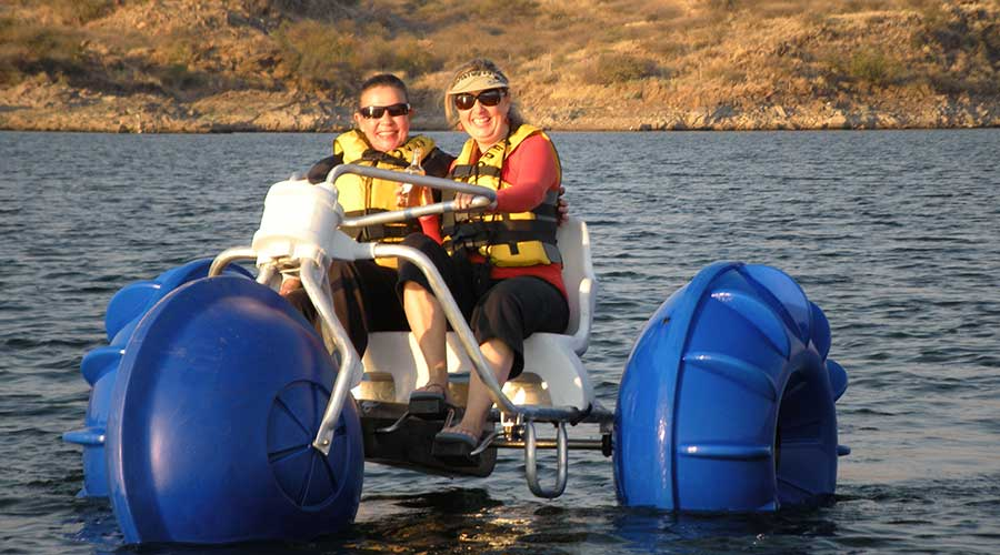 A big wheeled blue Aqua-Cycle™ Water Trikes at a lake recreational facility in a city with two ladies smiling while on the water tricycle.