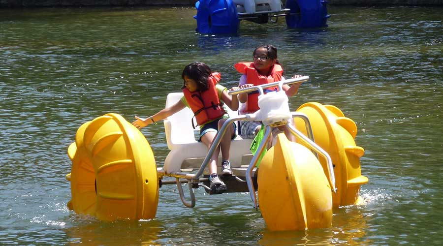 A big wheeled yellow Aqua-Cycle™ Water Trikes at a pond at a park recreational facility in a city with two young girls smiling while riding on the water tricycle.