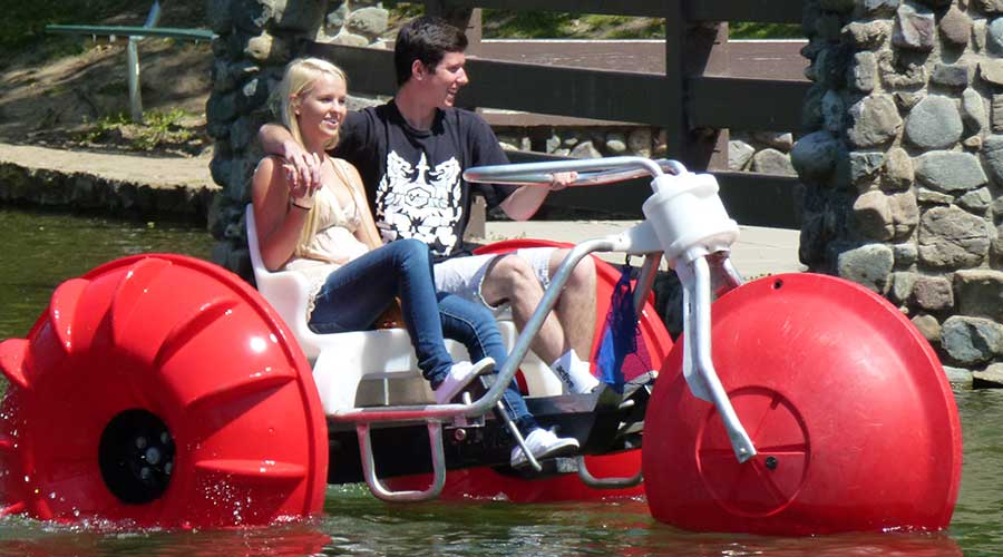 Young man with arm around girl on a big wheeled red Aqua-Cycle™ Water Trikes at a pond at a park recreational facility.