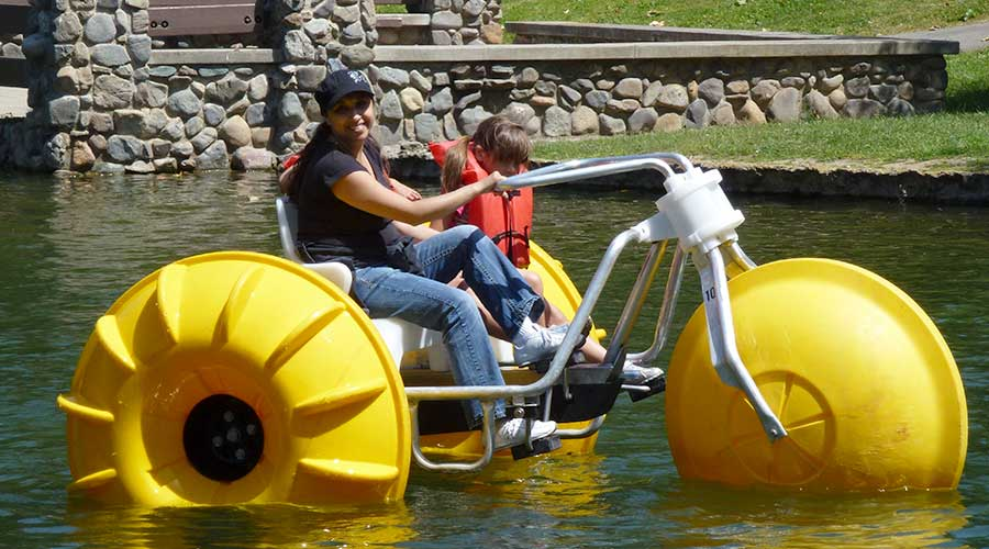 Mother and daughter on a big wheeled yellow Aqua-Cycle™ Water Trikes at a pond at a park recreational facility.