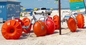 Orange Aqua-Cycle™ Water Trikes at a beach equipment rental business